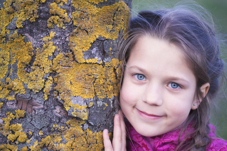 face in tree bark: smiling child girl close to mossy chestnut tree stem
