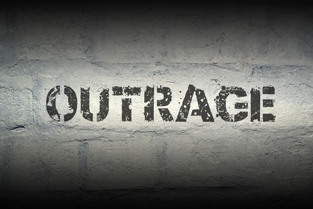 outrage stencil print on the grunge white brick wall; specially designed font is used