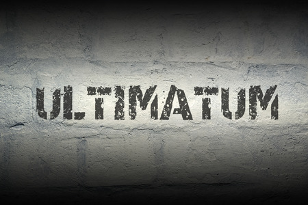 ultimatum stencil print on the grunge white brick wall; specially designed font is used