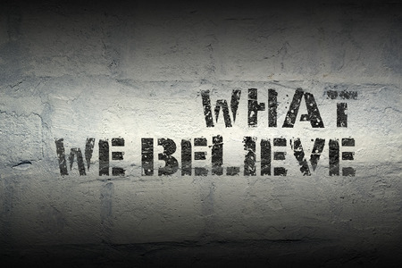 what we believe stencil print on the grunge white brick wall