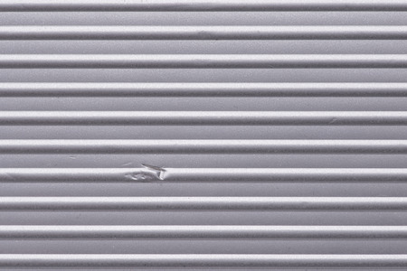 dint: corrugated metallic surface with small dent, horizontal orientation