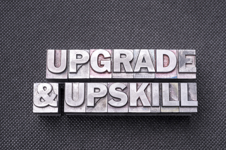 upgrade and upskill phrase made from metallic letterpress blocks on black perforated surface