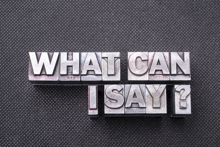 what can I say question made from metallic letterpress blocks on black perforated surface Stock Photo
