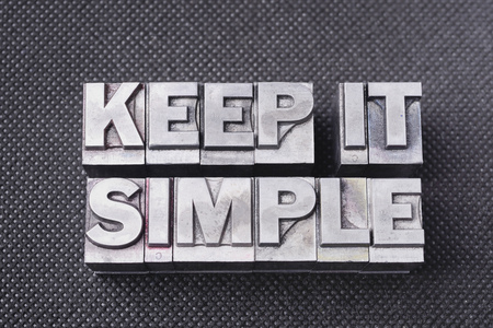 keep it simple phrase made from metallic letterpress blocks on black perforated surface Stock Photo
