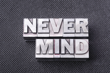 never mind phrase made from metallic letterpress blocks on black perforated surface Stock Photo