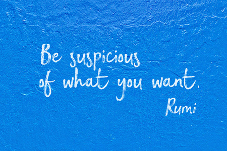 Be suspicious of what you want - ancient Persian poet and philosopher Rumi quote handwritten on blue wall