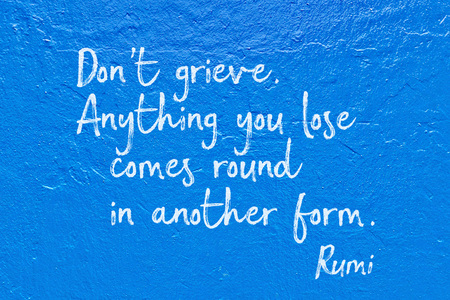 Don't grieve. Anything you lose comes round in another form - ancient Persian poet and philosopher Rumi quote handwritten on blue wall Stock Photo