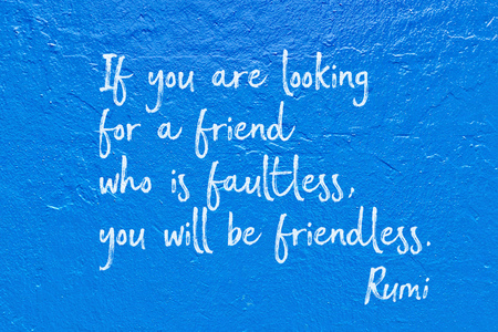 If you are looking for a friend who is faultless, you will be friendless - ancient Persian poet and philosopher Rumi quote handwritten on blue wall Stock Photo