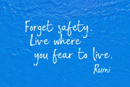Forget safety. Live where you fear to live - ancient Persian poet and philosopher Rumi quote handwritten on blue wall