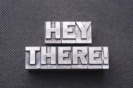 hey there exclamation made from metallic letterpress blocks on black perforated surface
