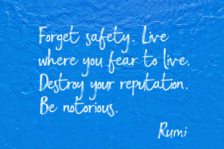 Destroy your reputation. Be notorious - ancient Persian poet and philosopher Rumi quote handwritten on blue wall