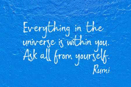 horisontal: Everything in the universe is within you - ancient Persian poet and philosopher Rumi quote handwritten on blue wall