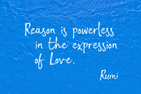 Reason is powerless in the expression of Love - ancient Persian poet and philosopher Rumi quote handwritten on blue wall Stock Photo