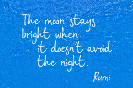 The moon stays bright when it doesnt avoid the night - ancient Persian poet and philosopher Rumi quote handwritten on blue wall