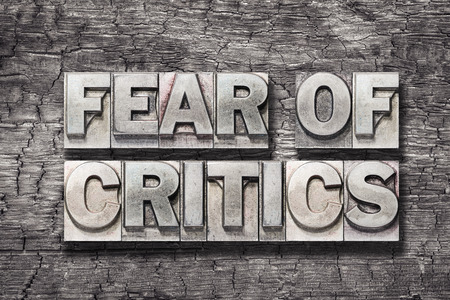 fear of critics phrase made from vintage letterpress type on burned wood background Stock fotó