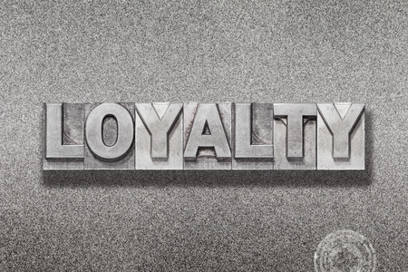 loyalty word made from vintage letterpress on metallic textured background