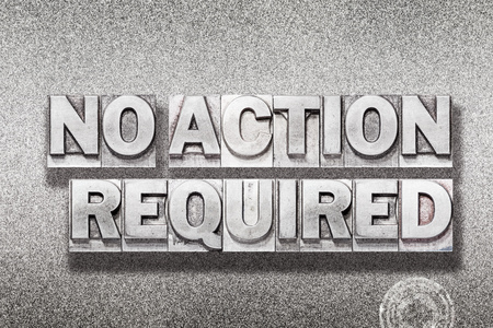 no action required phrase made from vintage letterpress on metallic textured background