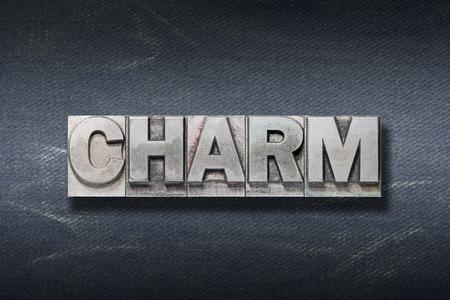 charm word made from metallic letterpress on dark jeans background Stok Fotoğraf