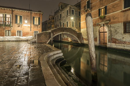 Venice quiet night with empty square and Ruga Vecchia bridge over water channel