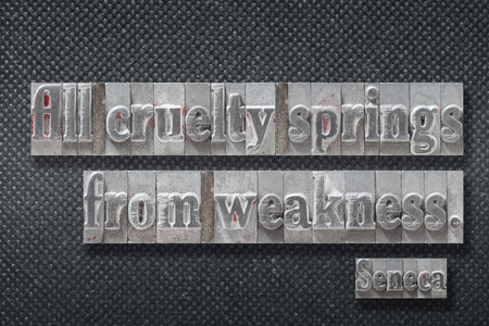 All cruelty springs from weakness - ancient Roman philosopher Seneca quote made from metallic letterpress on dark background