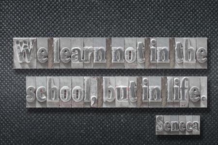 We learn not in the school, but in life - ancient Roman philosopher Seneca quote made from metallic letterpress on dark background Banco de Imagens