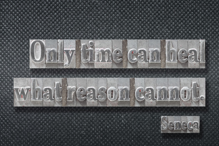 Only time can heal what reason cannot - ancient Roman philosopher Seneca quote made from metallic letterpress on dark background Banco de Imagens