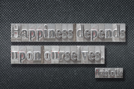 Happiness depends upon ourselves - ancient Greek philosopher Aristotle quote made from metallic letterpress on dark background 版權商用圖片