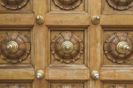 wooden floral ornament on massive door of Hindu temple in Singapore Stock Photo