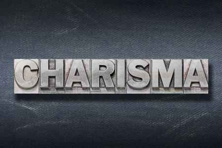 charisma word made from metallic letterpress on dark jeans background