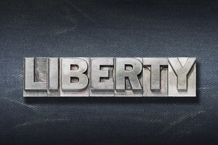 liberty word made from metallic letterpress on dark jeans background