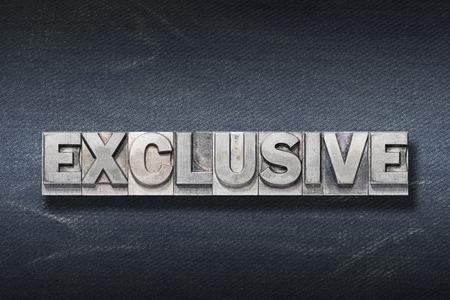 exclusive word made from metallic letterpress on dark jeans background