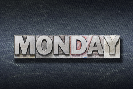 Monday word made from metallic letterpress on dark jeans background Stock Photo