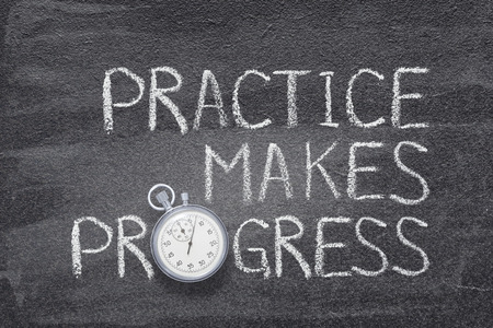 practice makes progress phrase handwritten on chalkboard with vintage precise stopwatch used instead of O
