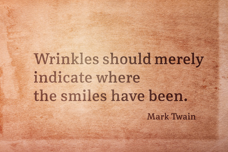 Wrinkles should merely indicate where the smiles have been - famous American writer Mark Twain quote printed on vintage grunge pape 版權商用圖片
