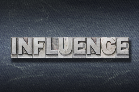 influence word made from metallic letterpress on dark jeans background 写真素材