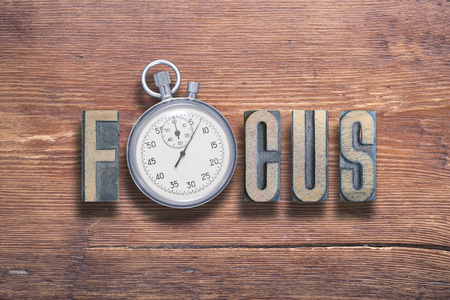 focus word combined on vintage varnished wooden surface with stopwatch inside
