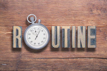 routine word combined on vintage varnished wooden surface with stopwatch inside Stock fotó