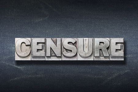 censure word made from metallic letterpress on dark jeans background