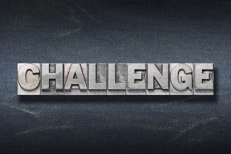 challenge word made from metallic letterpress on dark jeans background