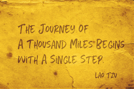 The journey of a thousand miles begins with a single step - ancient Chinese philosopher Lao Tzu quote printed on grunge yellow paper