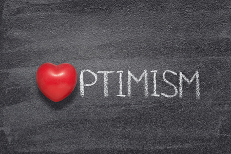 optimism word handwritten on chalkboard with red heart symbol instead of O