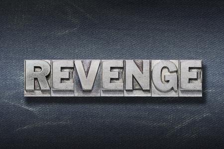 revenge word made from metallic letterpress on dark jeans background Stock fotó
