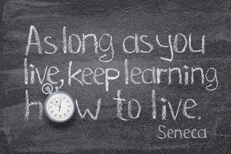 As long as you live, keep learning how to live - quote of ancient Roman philosopher Seneca written on chalkboard with vintage stopwatch instead of O