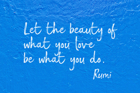 Let the beauty of what you love be what you do - ancient Persian poet and philosopher Rumi quote handwritten on blue wall