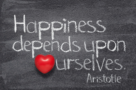 Happiness depends upon ourselves - of ancient Greek philosopher Aristotle written on chalkboard with vintage stopwatch instead of O