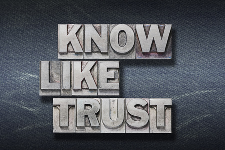 know, like, trust words made from metallic letterpress on dark jeans background Stock Photo