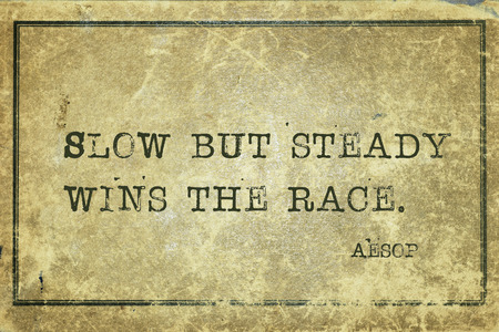 Slow but steady wins the race - famous ancient Greek story teller Aesop quote printed on grunge vintage cardboard