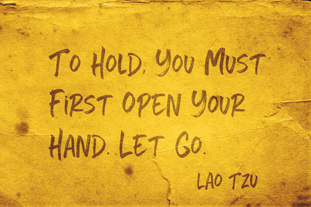 To hold, you must first open your hand - ancient Chinese philosopher Lao Tzu quote printed on grunge yellow paper