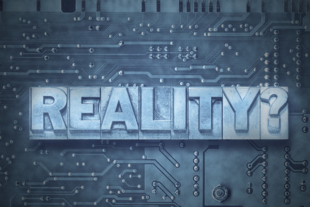 reality question made from metallic letterpress blocks on the pc board background Фото со стока