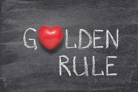 golden rule phrase handwritten on chalkboard with red heart symbol instead of O